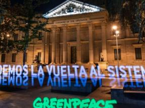 Greenpeace despliega una pancarta de luz frente al Congreso para pedir la transformación del sistema en clave verde